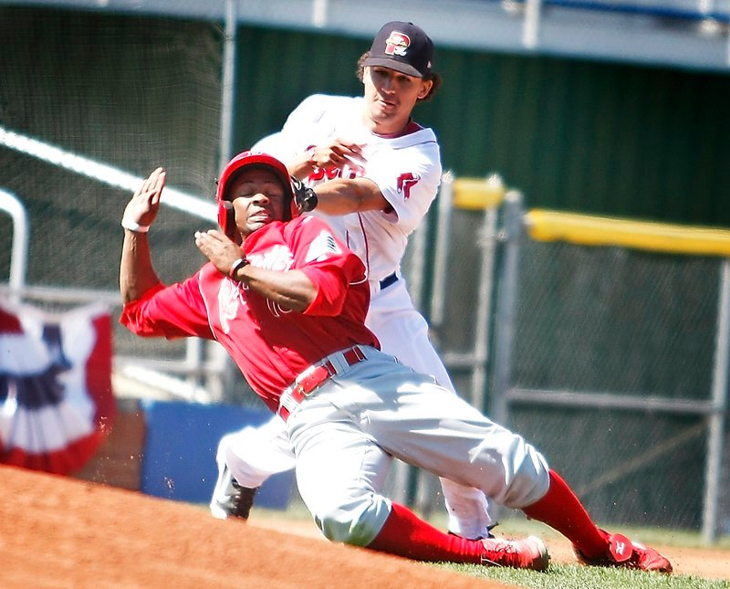 Derrik Gibson of the Sea Dogs attempts to tag Reading's Leandro Castro during a rundown in Monday's game at Hadlock Field. Castro was called safe at third. The Dogs lost, 7-3.