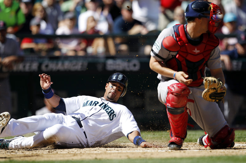 Franklin Gutierrez of the Mariners slides safely into home behind Red Sox catcher Ryan Lavarnway, part of a four-run rally in the fourth inning that gave Seattle a 4-1 victory.