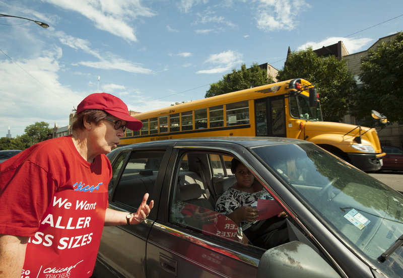 A member of the Chicago Teachers Union asks a parent for support in ongoing contract talks with the Board of Education, during an informational picket last month outside Willa Cather Elementary School in Chicago. The city's teachers and support staff are prepared to strike next Monday.
