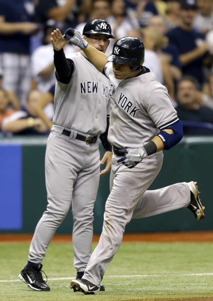 The Yankees' Russell Martin, right, high-fives third-base coach Rob Thomson after his sixth-inning homer in a 6-4 win Wednesday over the Tampa Bay Rays.