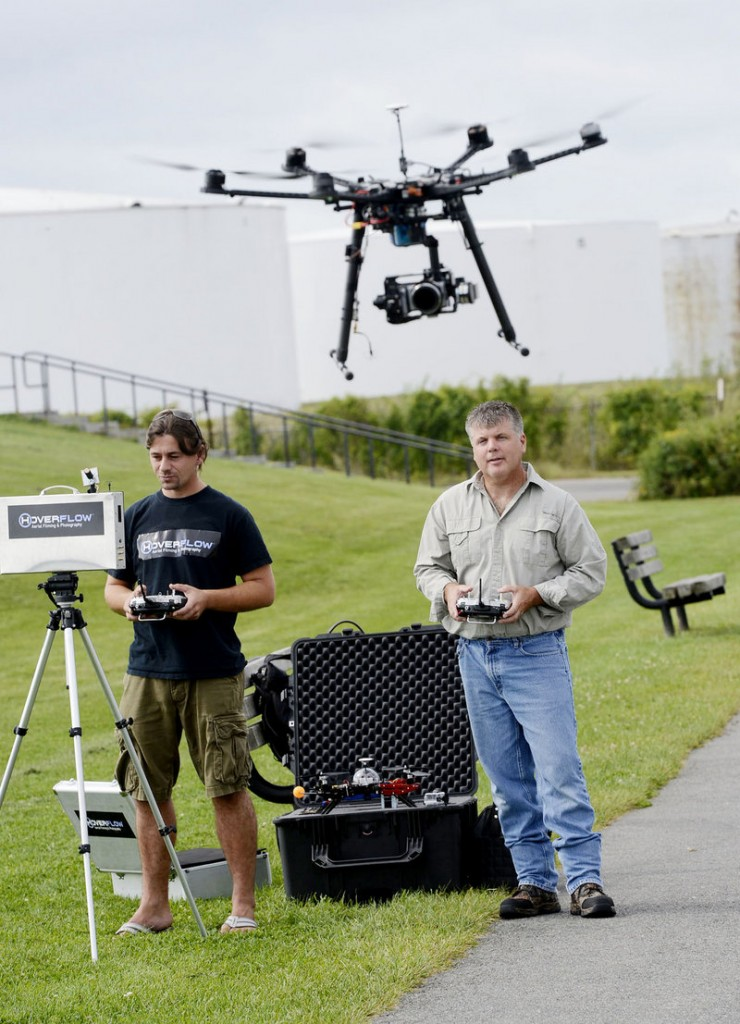 Chris Trafford, left, operates the camera and Rob Mitchell guides the drone carrying the camera as the HoverFlow owners take aerial photos in South Portland on Thursday.