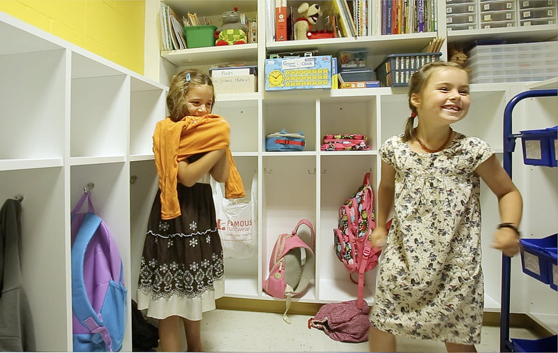 Nora Grace Monaghan puts a t-shirt over her dress while classmate Stella Halstead laughs in the cubby area of their new classroom during the first day of school at East End School in Portland on Thursday, Sept. 6, 2012.