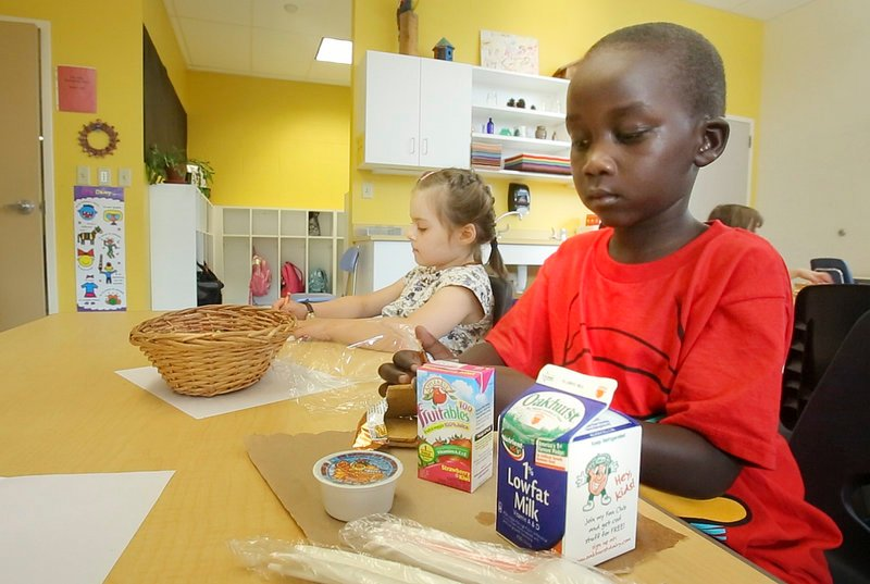 First-grader Junior Eda opens his graham crackers while eating breakfast in his classroom at East End School in Portland on Thursday, September 6, 2012.
