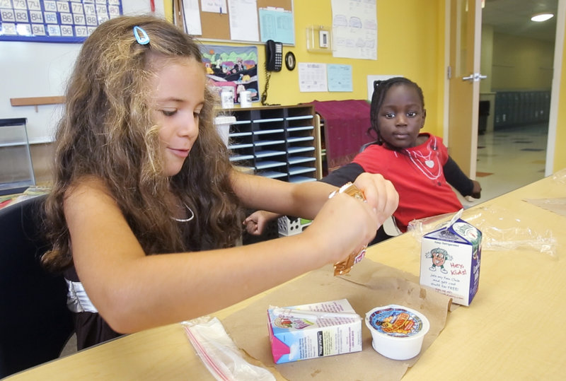 First-grader Nora Grace Monaghan opens up her graham crackers while eating breakfast in her classroom at East End School in Portland on Thursday, Sept. 6, 2012. At right is her classmate Junisia Oromo.