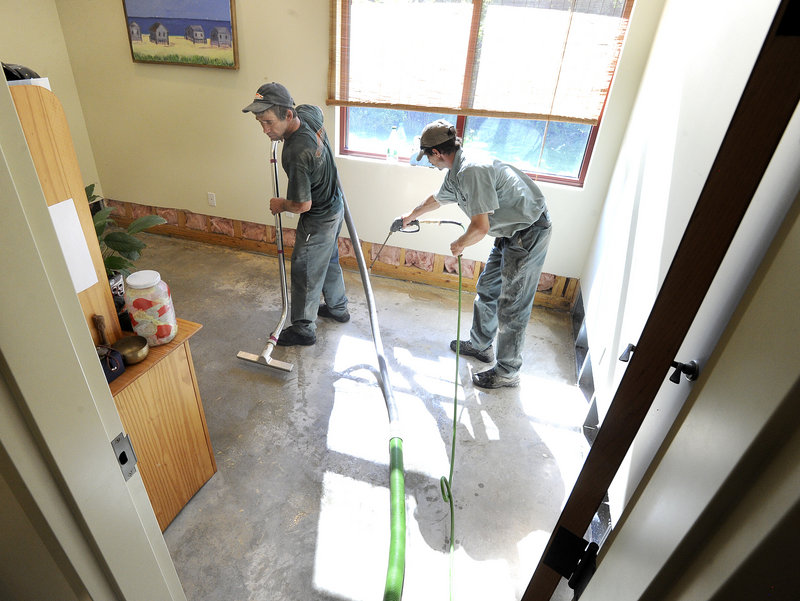 Roger Piper and Dave Ryan with Servpro clean Greener Postures Yoga on Friday after a water main break caused heavy damage to several South Portland businesses along Broadway.