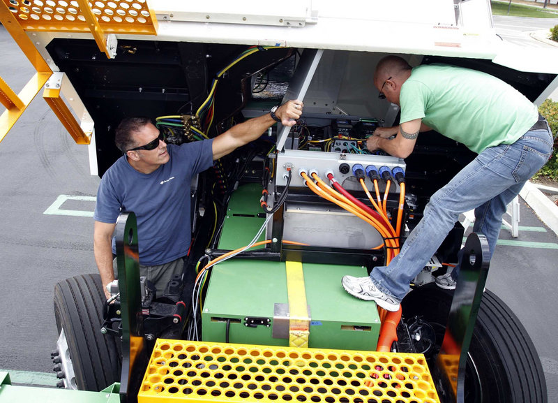 Frank Falcone, left, and Ian Springer work on one of two electric truck prototypes showcased along with other new technologies at an annual event put on by PortTechLA.