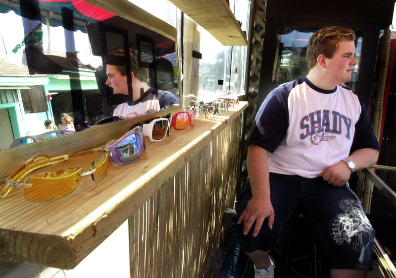 A teenage employee awaits customers at a sunglass shop on the pier in Old Orchard Beach in July 2004. School districts that start the school year before Labor Day and government programs that fill summer jobs with foreign students present obstacles to young people seeking seasonal work, a reader says.