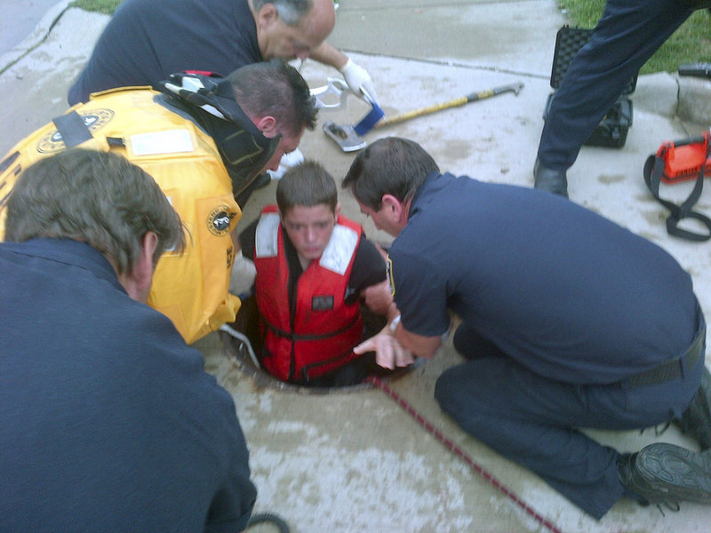 Firefighters rescue 14-year-old Jeffrey LaPorta from a manhole Tuesday in Parma, Ohio, in this photo supplied by the fire department. Authorities say LaPorta fell off his bike, was swept by flood waters into city sewer pipes, and traveled more than a quarter of a mile, at times completely submerged, before he found enough breathing room to await rescue.