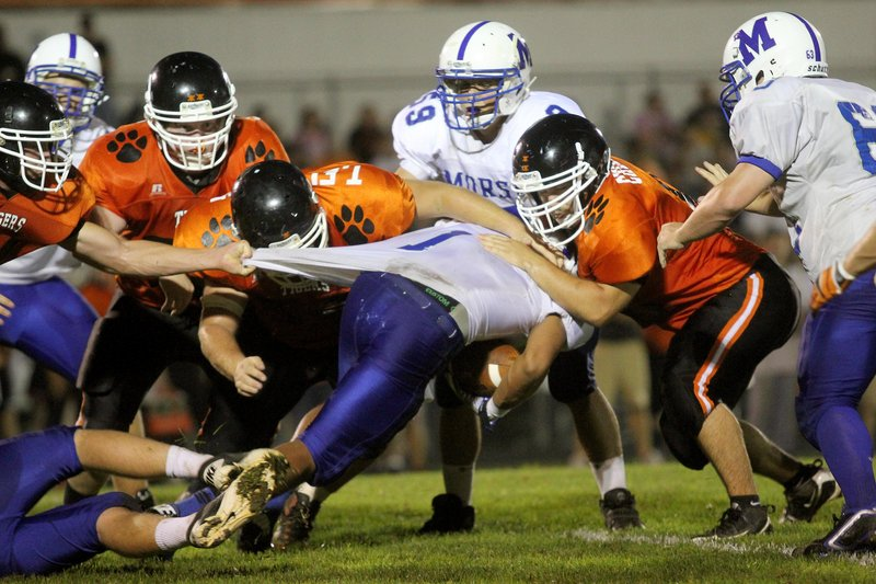 D'Vaughn Meyers of Morse gets his shirt pulled Friday night. Mitch Chesley makes the tackle for Gardiner, which won, 31-8.