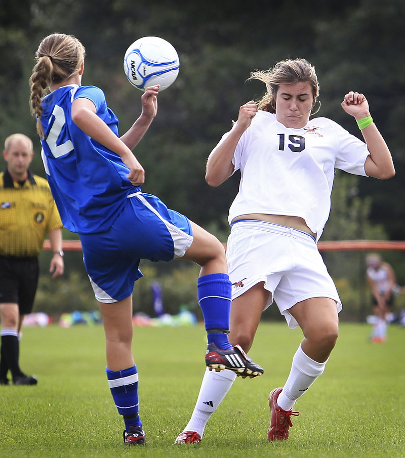 Libby Arford, right, of Brunswick attempts to block a shot by Sonja Robert of Mt. Ararat. Brunswick took command with three goals in the first 20 minutes.