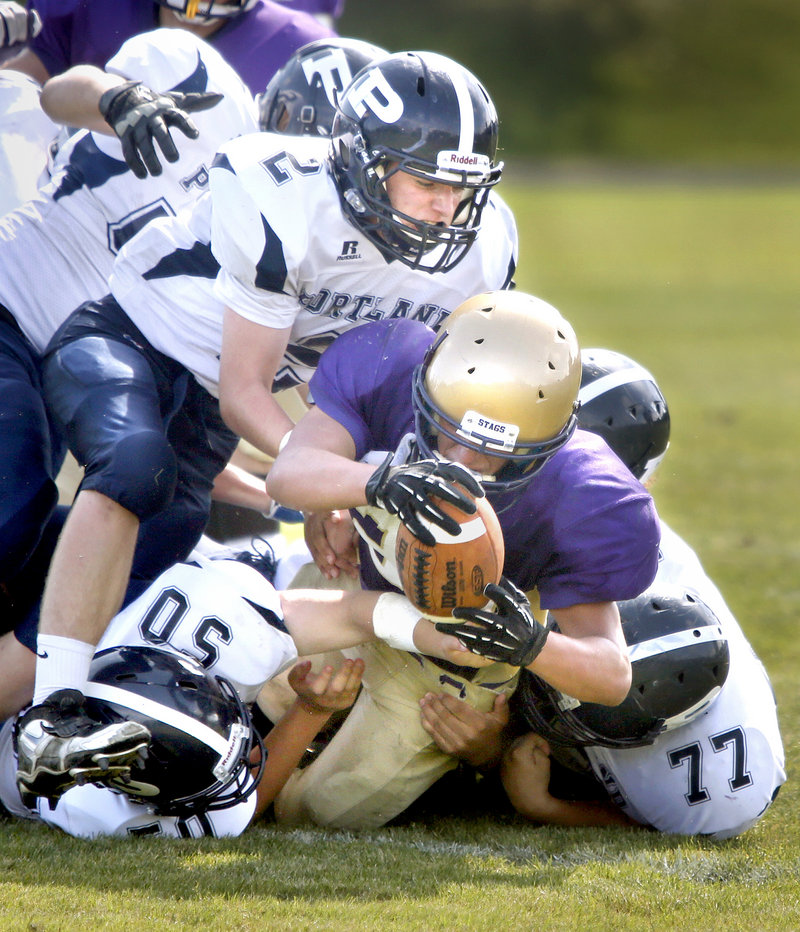 Cheverus running back Cody O'Brien is tackled by Portland's Anthony Lane, bottom left, Joe Nielsen, top, and Cody McCormack. Cheverus won, 42-0.