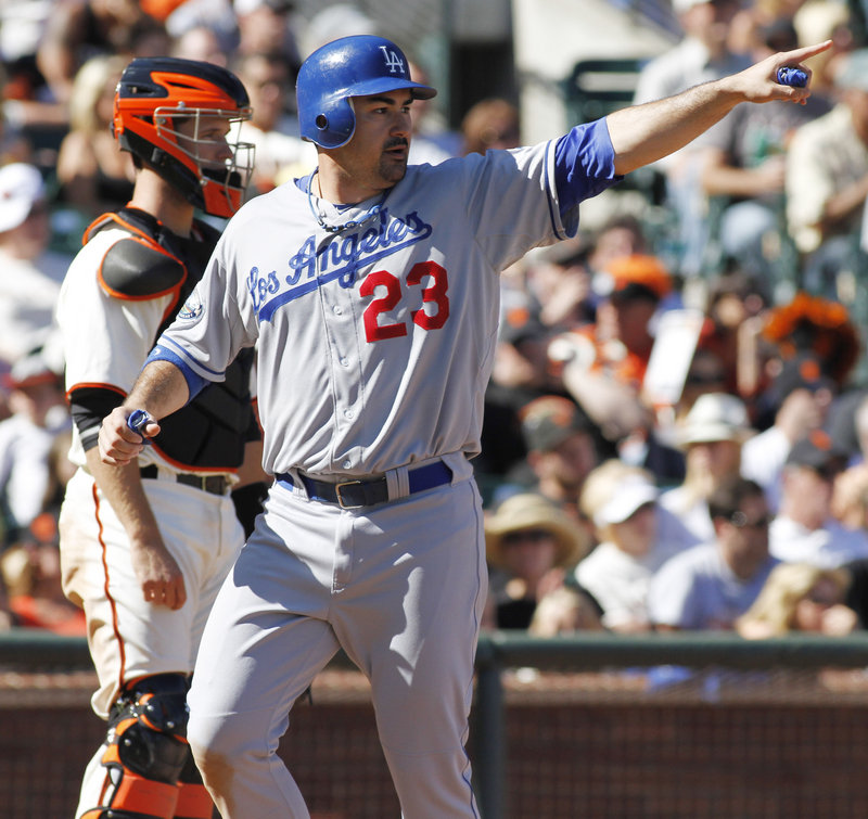 Adrian Gonzalez points to Hanley Ramirez after scoring the go-ahead run on a double by Ramirez in the ninth inning, giving the Dodgers a 3-2 win Saturday over the Giants.