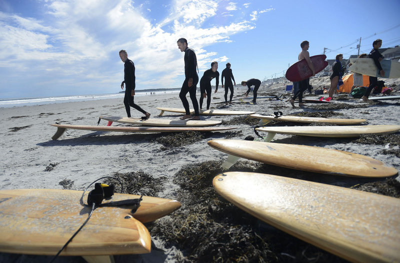 Surfers including Rand Budd, left, of West Creek, N.J., and Bob Paradis, second from left, of Saco look over wooden surfboards on the beach during the second annual Surf Re-Evolution festival at Long Sands Beach in York on Sunday.