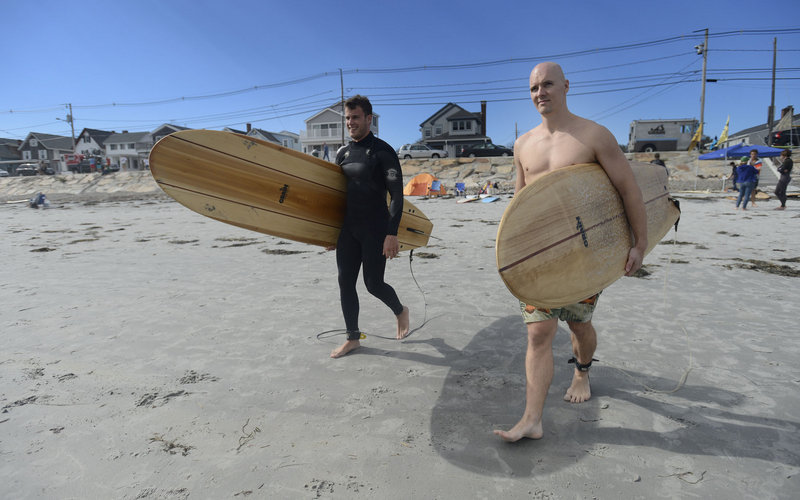 Ben Many of Portland, left, and Lloyd Hall of Biddeford make their way to the ocean carrying Grain Surfboards during the second annual Surf Re-Evolution festival at Long Sands Beach in York on Sunday.