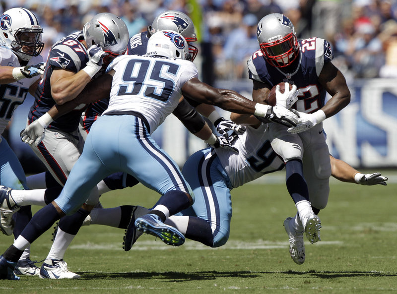 Stevan Ridley, the Patriots' new featured running back, tries to breakaway from Kamerion Wimbley (95) and Karl Klug (97) of the Titans. Ridley rushed for 125 yards.