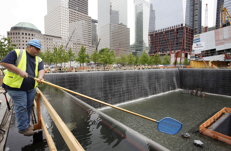 Anthony St. Jeanos uses a net to skim debris from the water during a test of the waterfalls at the National Sept. 11 Memorial and Museum at the World Trade Center site in New York. The site may not be complete until at least 2014.