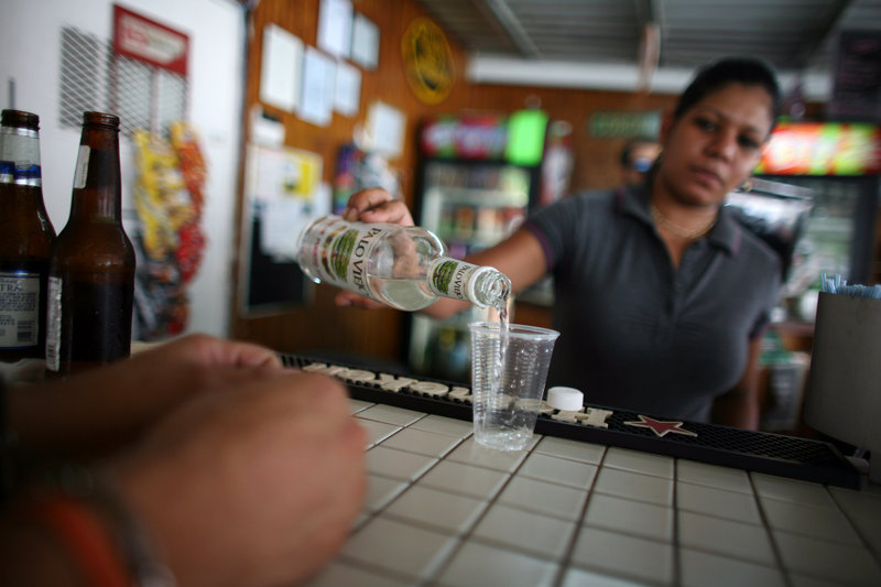 A bartender fills a glass with rum at a bar in San Juan, Puerto Rico. Small producers in countries such as Antigua, Guyana and Jamaica complain they are being pinched by unfair trade and marketing advantages for global beverage corporations operating in U.S. territories.