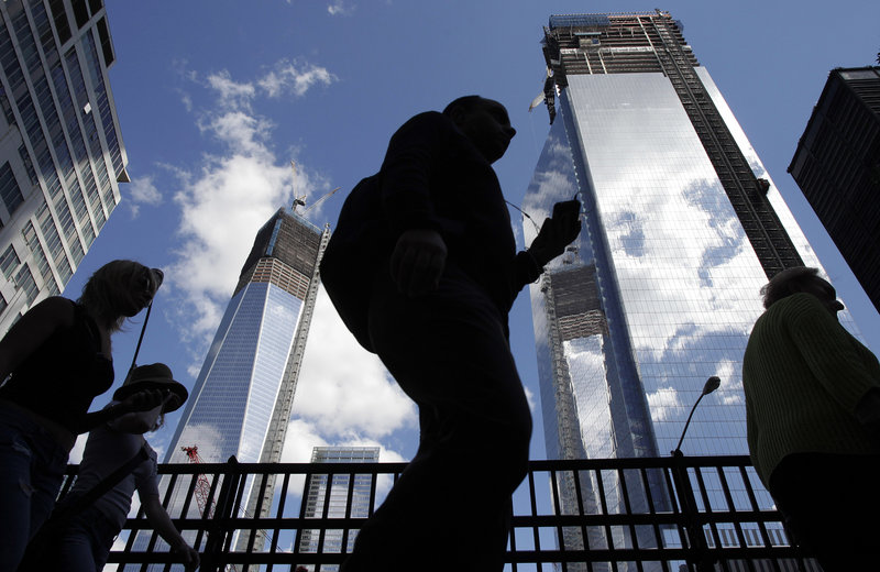 Visitors to the National September 11 Memorial walk Monday below the rising towers of 1 World Trade Center, left, and 4 World Trade Center. Tuesday will mark the 11th anniversary of the attacks of Sept. 11, 2001.