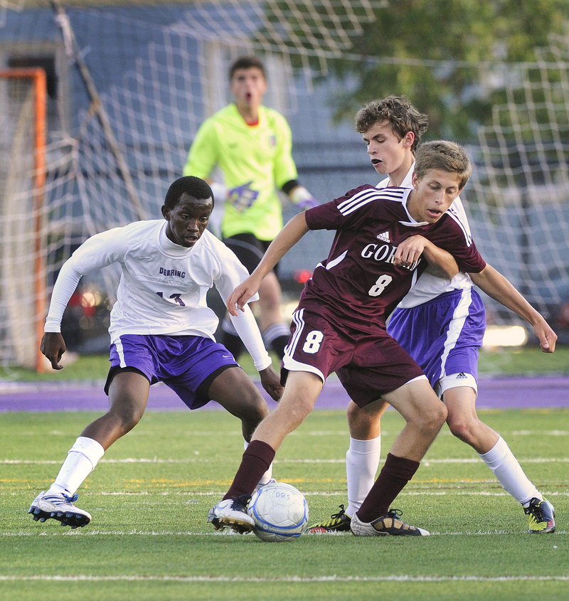 Jonathan Bujambi, left, and Jimmy Fasulo of Deering try to take the ball away from Gorham's Spence Cowand.