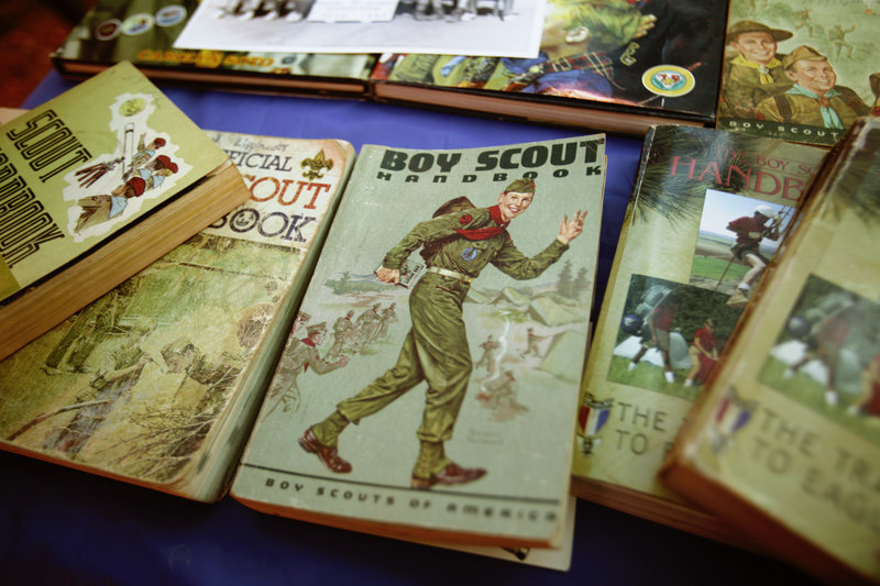 Boy Scout handbooks from over the years are shown at a campsite. Readers debate the value of proposals to change the Scouts' policies on the involvement of gays.