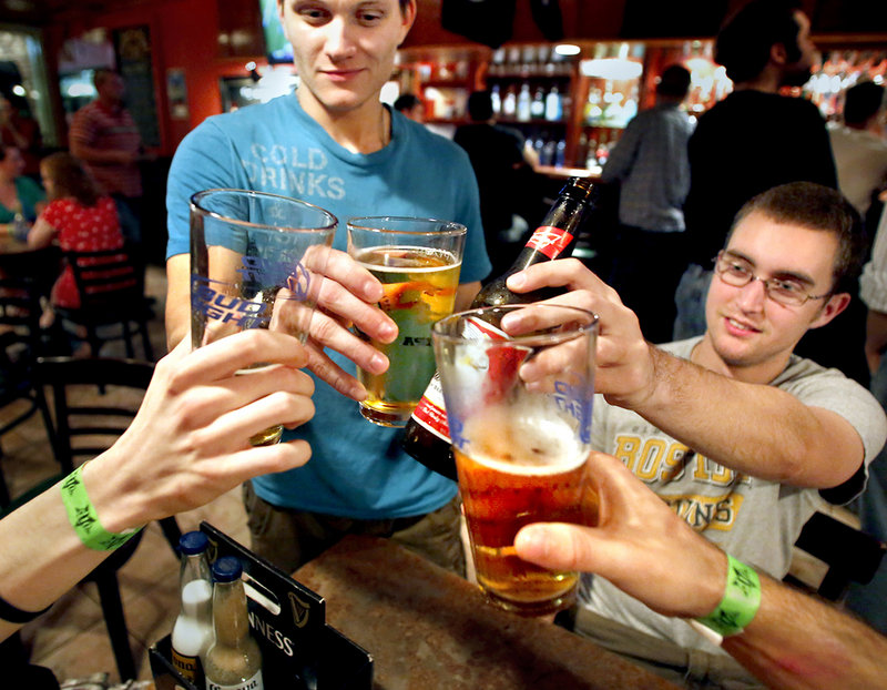 """Joseph Miller, a UMaine senior from Topsham, left, and fellow senior Andy Bepuain of Bangor toast with friends at the Bear Brew Pub in Orono on a recent Friday night. """"I think people party almost out of necessity,"""" Miller said."""
