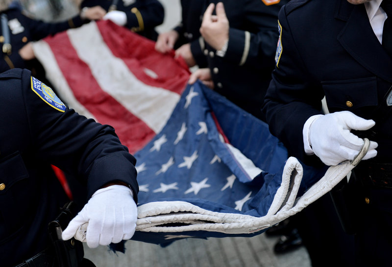 Police officers of the Port Authority of New York and New Jersey carry a U.S. flag that once flew over the World Trade Center towers.