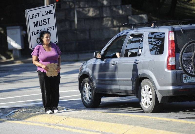 A woman panhandles from the median at the intersection of St. John Street and Park Avenue in Portland in July.