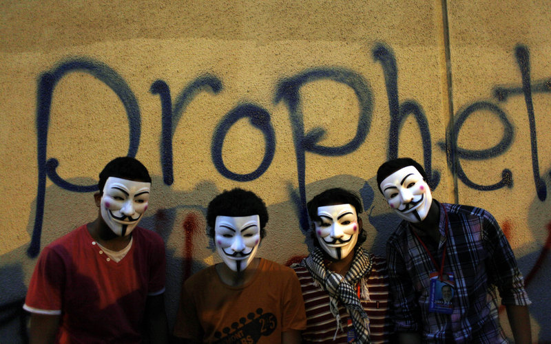 Egyptian protesters wearing Guy Fawkes masks pose Tuesday in front of a wall of the U.S. embassy in Cairo. The protest was sparked by a YouTube film deemed offensive of Islam.