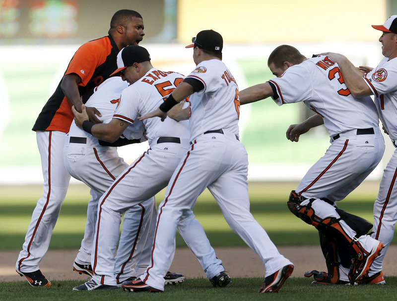 The Baltimore Orioles continue to stay hot, as they mob Manny Machado, second from left, after his 14th-inning single beat the Tampa Bay Rays 3-2 at Baltimore on Thursday.
