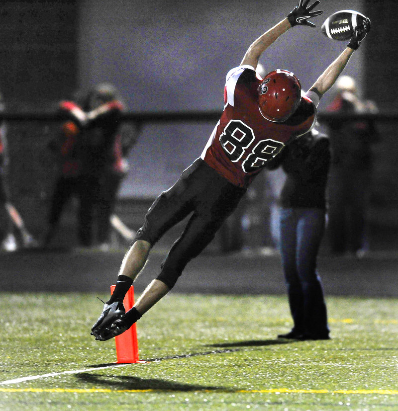 Greg Viola of Scarborough leaps to haul in a pass from Dillon Russo in the end zone Friday night, completing a 30-yard play in the first quarter and giving the Red Storm their second touchdown on the way to a 27-12 victory against Windham.
