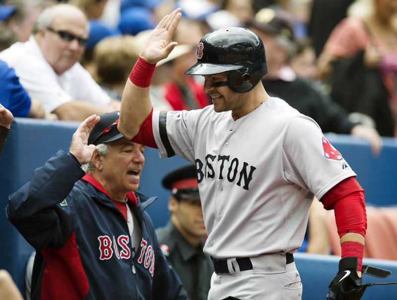 Boston's Cody Ross has a high-five ready as he heads to the dugout after his leadoff homer in the second inning – his 21st of the year – in the 3-2 win at Toronto on Saturday.