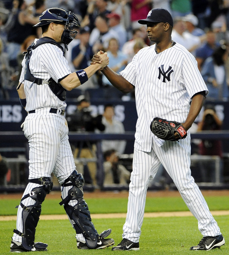 Yankees closer Rafael Soriano celebrates with catcher Chris Stewart after finishing off a 5-3 win over Tampa Bay that kept New York in first place in the AL East.