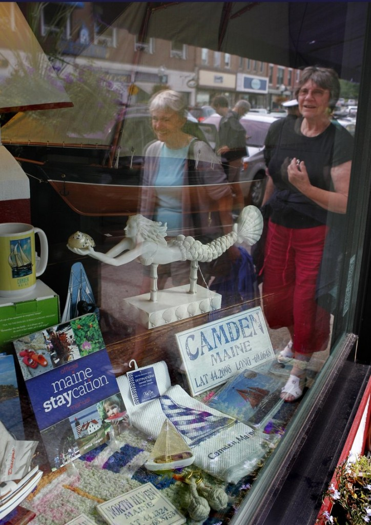 "A book titled ""Maine Staycation"" sits on display in a storefront in Camden."