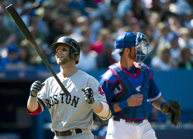 Boston's Dustin Pedroia flips his bat after striking out in the third inning of a 5-0 shutout at Toronto on Sunday. The Red Sox squandered chances early in the game, putting runners in scoring position in three of the first four innings.
