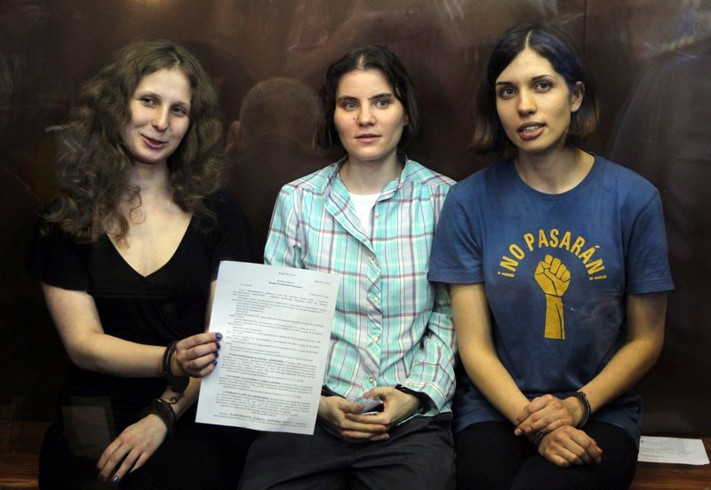"Members of the feminist punk group Pussy Riot, from left, Maria Alekhina, Yekaterina Samutsevich and Nadezhda Tolokonnikova, are seen this summer inside a glass cage at a courtroom in Moscow where they were convicted of ""hooliganism"" and sentenced to two years in prison."