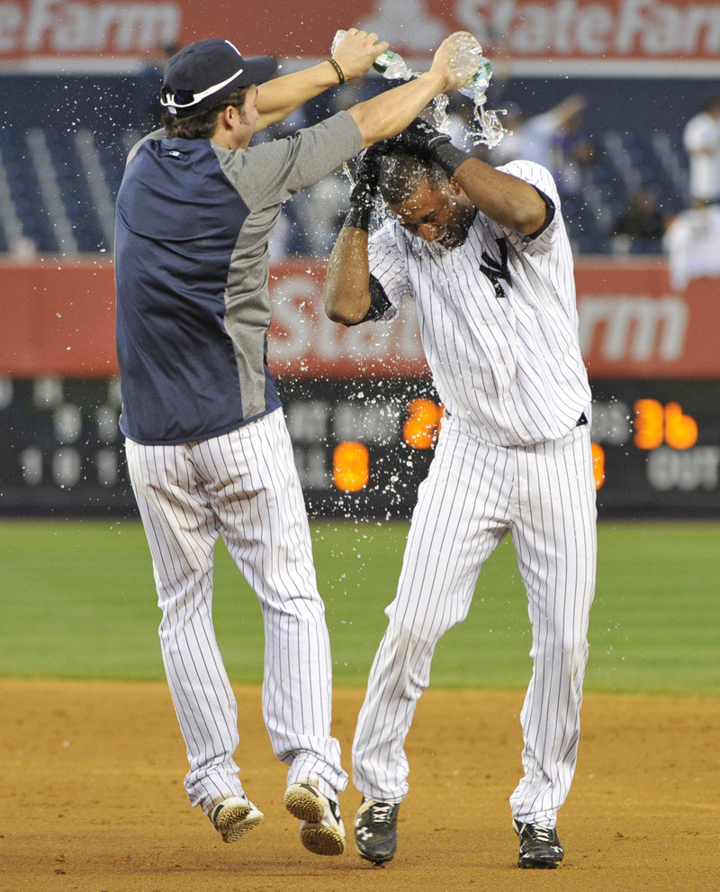 Eduardo Nunez, right, celebrates with Nick Swisher after the Yankees rallied to beat Oakland 10-9 in 14 innings Saturday.