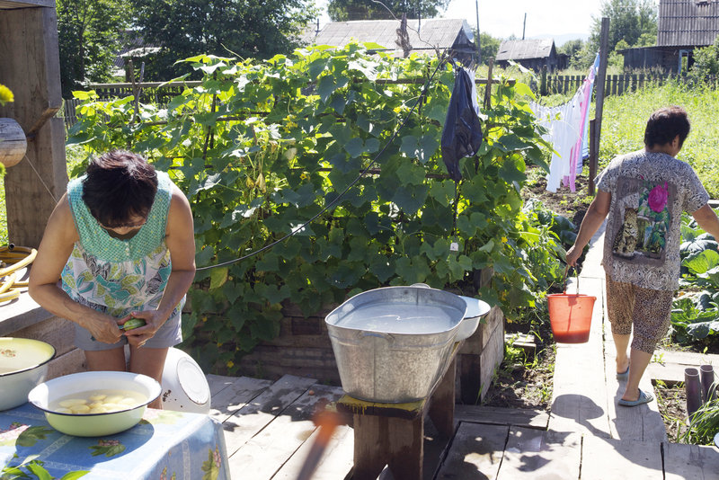 During summer months, the kitchen is moved outdoors. Here, Svetlana is peeling potatoes while her sister, Valya Zharavleva takes kitchen scraps to her compost pile at the edge of the garden.