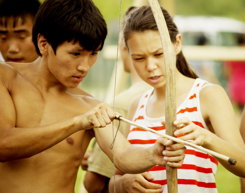A village boy, Yura Kunchuga, teaches Ihila to use a bow and arrow during a competition at the summer festival.