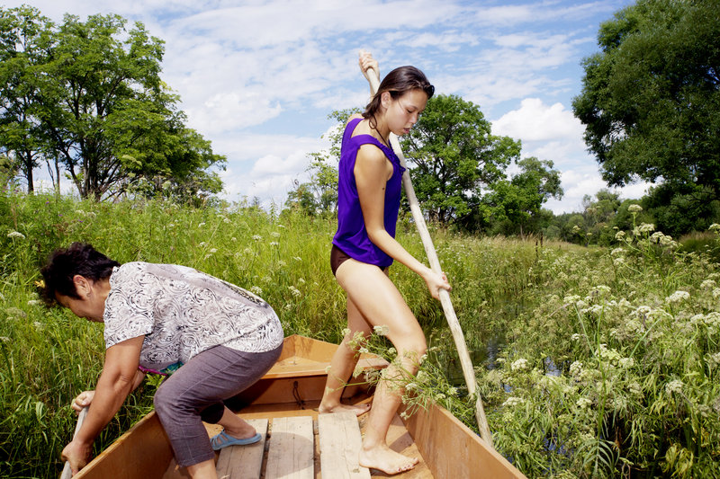 Ihila and her aunt, Valya Zhuravleva, use poles to propel a flat-bottomed boat up a tributary of the Bikin River.