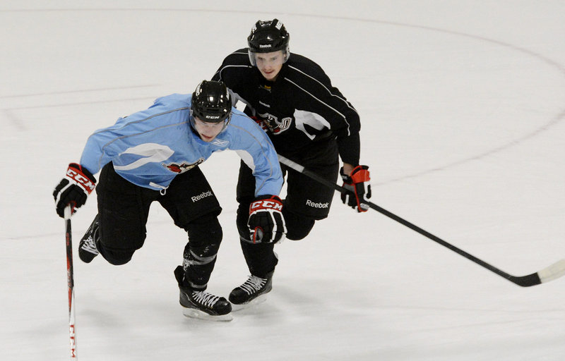 Oliver Ekman-Larsson, right, competes with Scott Arnold during drills Sunday at the Portland Pirates' training camp at the Portland Ice Arena.
