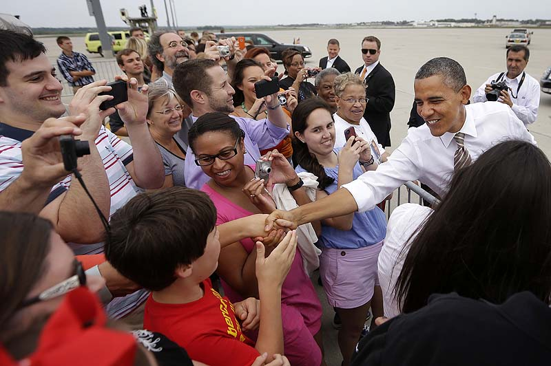 President Barack Obama greets guests on the tarmac upon his arrival at Des Moines International Airport, Saturday in Iowa.