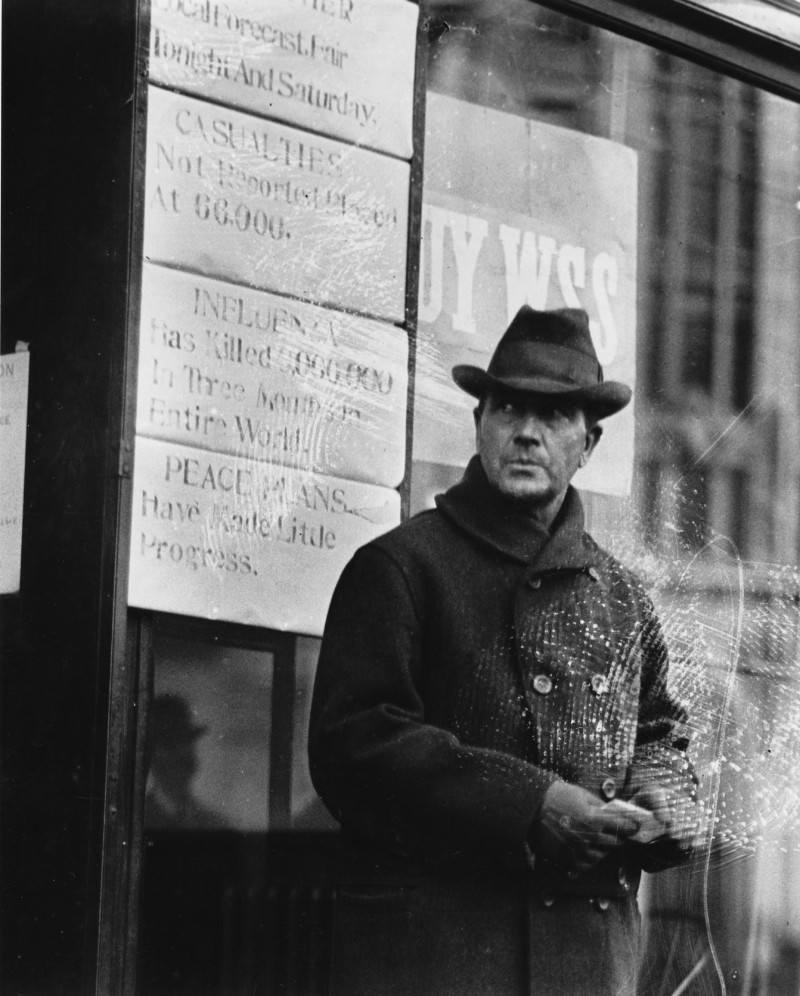 A man stands outside of the Press Herald/Telegram building during World War I. One of the signs behind him reads,
