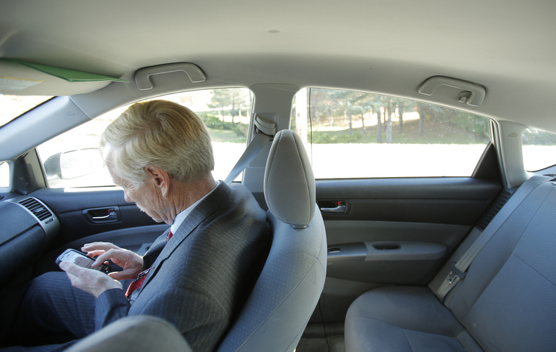 Independent Angus King checks his email while being driven between campaign events in Waterville.