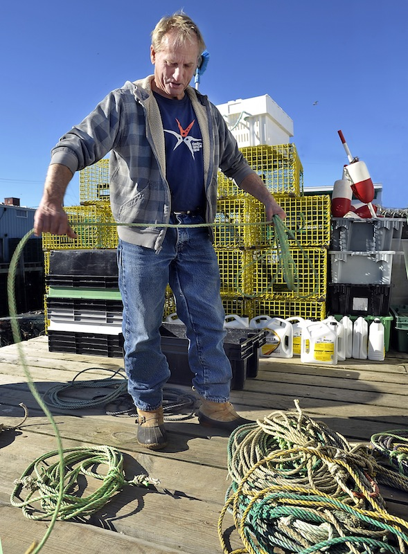 "Lobsterman Jim Holden, working on Widgery Wharf in Portland on Thursday, prepares to move his traps into deeper water in advance of next week's arrival of Hurricane Sandy. ""I think I lost 300 traps"" during the ""perfect storm"" of 1991, he said. ""I hope I don't get bit that bad again."""