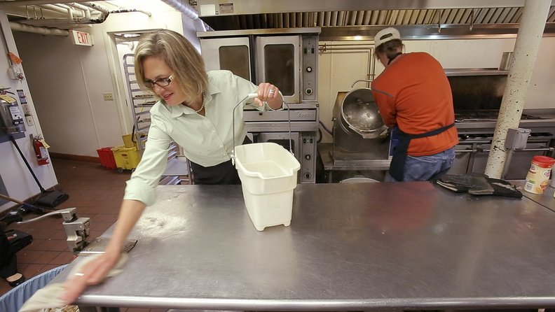 Democrat Cynthia Dill wipes down a kitchen counter while volunteering at the Preble Street center in Portland.