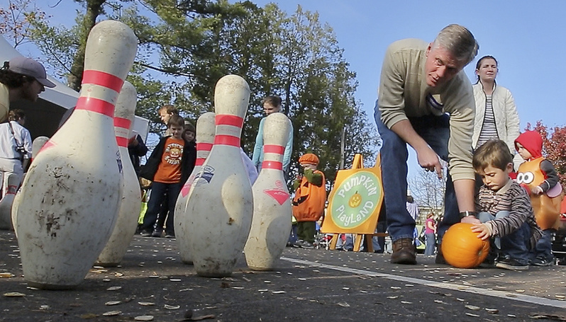Republican Charlie Summers helps his son Thomas bowl during the Camp Sunshine Pumpkin Festival at L.L. Bean in Freeport.