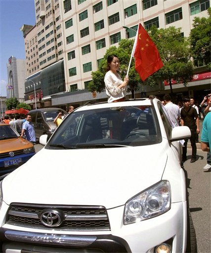 In this Sept. 15, 2012 photo, a woman holding a Chinese flag calls for protesters not to attack her Toyota car during the anti-Japan protest in Chongsha in China's Hunan Province. Toyota is shrugging off a sales plunge in China set off by a territorial dispute and says it is headed to a record year on the back of strong growth in the rest of Asia and the U.S. Toyota Motor Corp. Executive Vice President Yukitoshi Funo acknowledged Monday, Oct. 29 that achieving the company's target of 9.76 million vehicle sales this year will be harder because of the problems in China. Violent protests and a call to boycott Japanese goods erupted after Tokyo nationalized tiny islands that are controlled by Japan but claimed by Beijing. (AP Photo/Kyodo News) JAPAN OUT, MANDATORY CREDIT, NO LICENSING IN CHINA, FRANCE, HONG KONG, JAPAN AND SOUTH KOREA