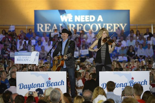 FILE - In this Oct. 19, 2012 file photo, country music singer John Rich, left, performs before Republican presidential candidate, former Massachusetts Gov. Mitt Romney and his vice presidential running mate Rep. Paul Ryan, R-Wis., arrived during the Romney Ryan Victory Rally in Daytona Beach, Fla. Dozens of celebrities, elected officials, and others are blitzing through battleground states in the White House race�s final days. Their goal: give the presidential campaigns a daily presence in key states even when the men at the top of the ticket (and their running mates) pitch for votes elsewhere. (AP Photo/Phelan M. Ebenhack, File)