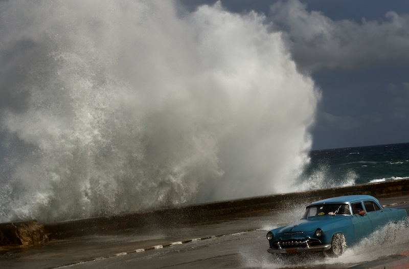 A driver maneuvers his classic American car along a wet road as a wave crashes against the Malecon in Havana on Thursday as Hurricane Sandy blasted across eastern Cuba.