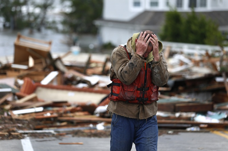 Brian Hajeski, 41, of Brick, N.J., reacts after looking at debris of a home that washed up on to the Mantoloking Bridge the morning after superstorm Sandy rolled through, Tuesday, Oct. 30, 2012, in Mantoloking, N.J. Sandy, the storm that made landfall Monday, caused multiple fatalities, halted mass transit and cut power to more than 6 million homes and businesses. (AP Photo/Julio Cortez)